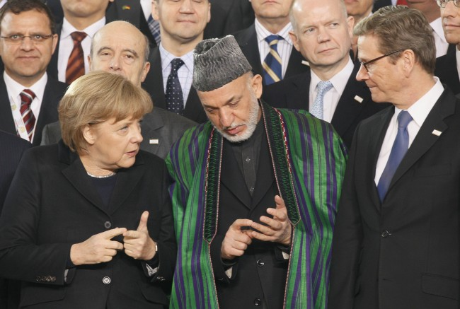 German Chancellor Merkel and Afghan President Karzai use their fingers to count during the family photo opportunity at the International Afghanistan Conference in Bonn