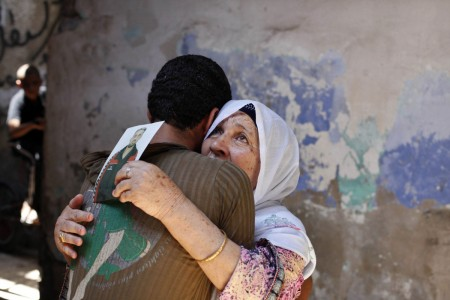 The mother of a Palestinian held prisoner by Israel reacts as she is hugged by her grandson in Khan Younis