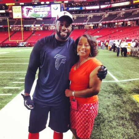 Brian Banks poses with his mother on the field before the Atlanta Falcons final preseason game.