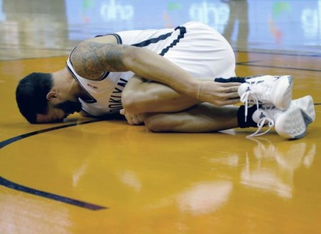 Brooklyn Nets guard Deron Williams grabs his ankle after rolling it in the first quarter on Friday.